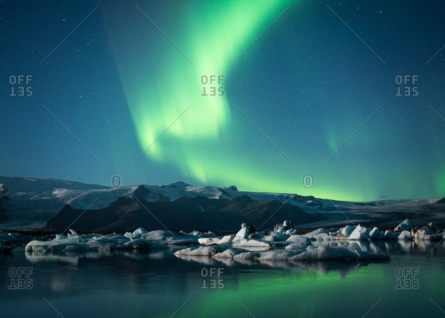 Aurora borealis over mountain landscape and water