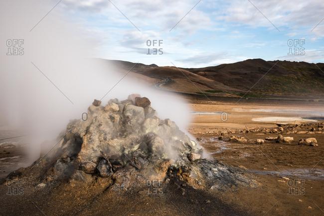 Steaming fumarole in desolate landscape