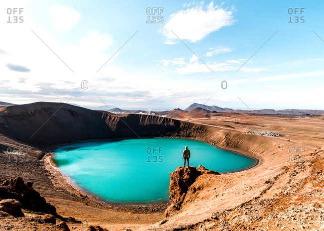 Person standing on rocky outcrop overlooking scenic lake in barren landscape