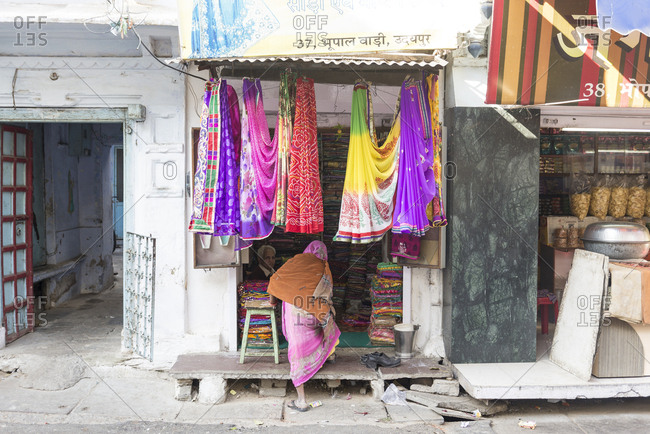 Udaipur, India - 5 July, 2012: Rearview of woman walking into store selling colorful fabrics