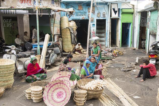 Udaipur, India - 5 July, 2012: Craftswomen weaving baskets in courtyard