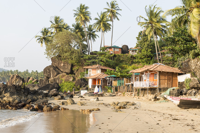 Goa, India - 29 July, 2012: Little bungalows tucked into the rocks of Palolem Beach