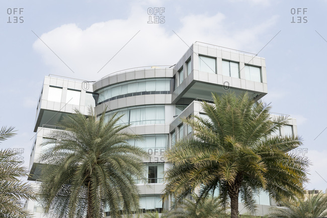 Bangalore, India - 08 August, 2012: Palm trees frame the facade of modern office building