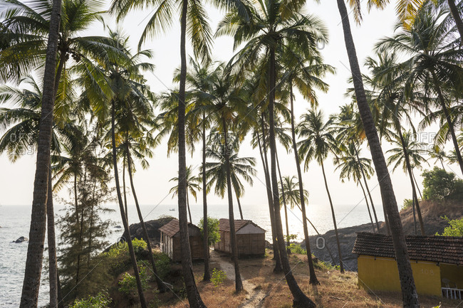 Goa, India - 29 July, 2012: Little bungalows perched on the rocks looking out to sea at Palolem Beach