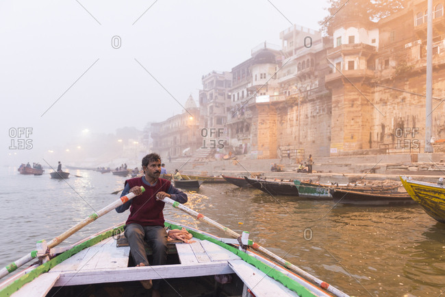 Varanasi, India - 21 June, 2012:  Boatman rowing with mist shrouding ghats and buildings along Ganges River