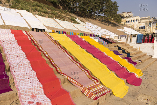Varanasi, India - 22 June, 2012:  Colorful fresh washed fabrics and clothes drying in the sun on the ghats on the Ganges River