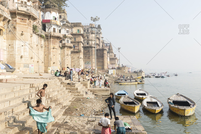 Varanasi, India - 22 June, 2012:  Local men bathing and washing clothes on the ghats on the Ganges River