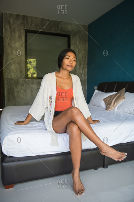 Asian woman sitting on hotel bed and thinking