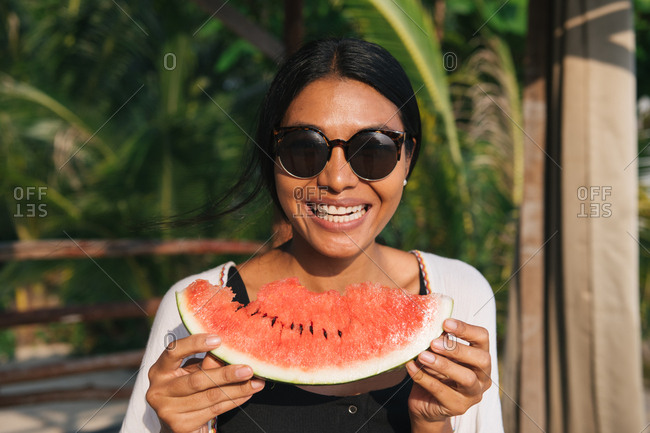 Smiley woman wearing sunglasses holding watermelon