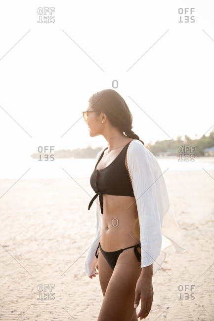 Young woman in swimsuit walking on the beach during sunset