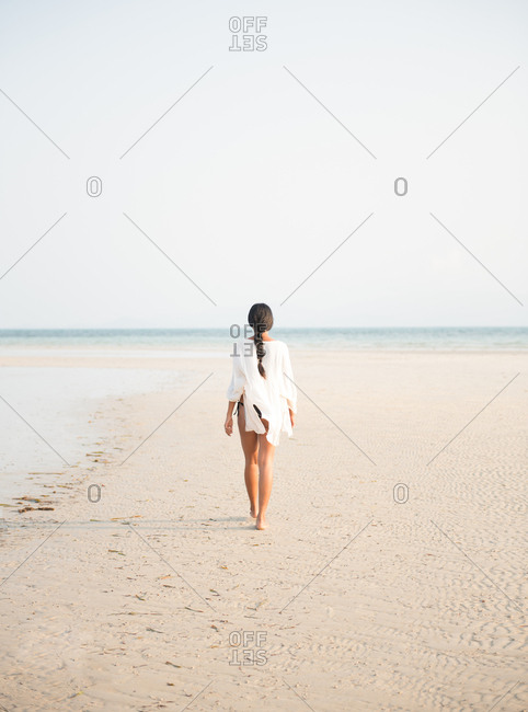 Young woman with long dark hair walking on the beach during sunset