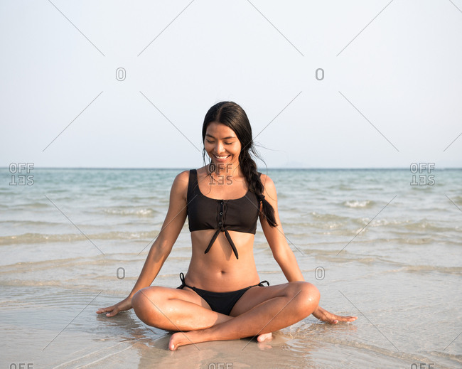 Asian lady sitting on the beach wearing swimsuit