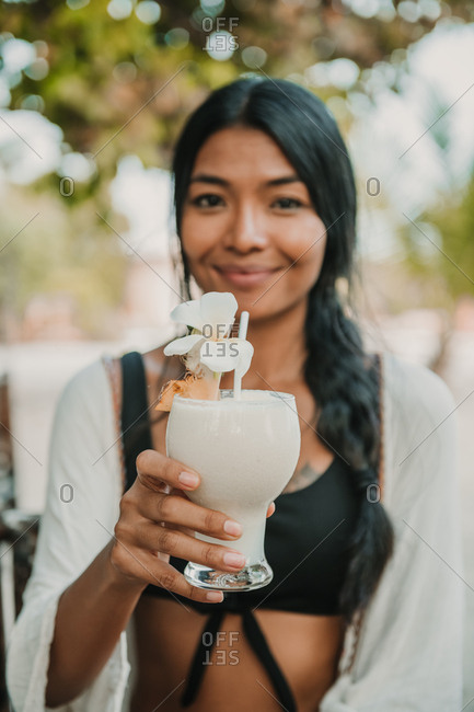 Thai girl holding a cocktail looking to the camera