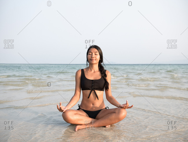 Asian woman doing meditation in the beach wearing swimsuit