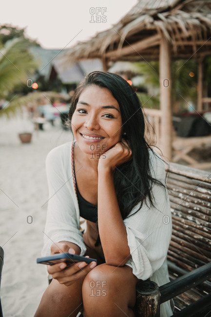 Asian woman smiling looking to the camera holding her phone