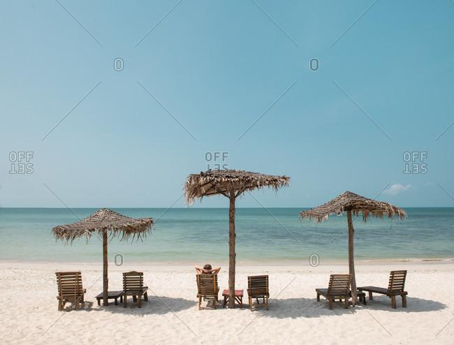 Woman laying near a straw umbrellas on the beach