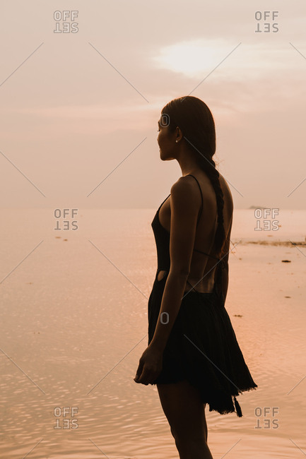 Silhouette of exotic woman with the sunset and sea
