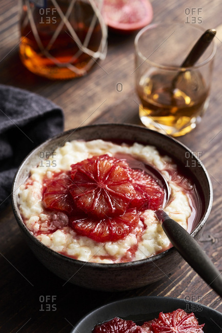 Sweet rice pudding with marinated blood oranges in ceramic bowl on dark wooden table