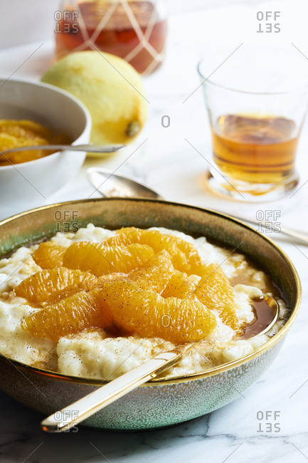 Sweet rice pudding with marinated oranges sprinkled with cinnamon on white marble table