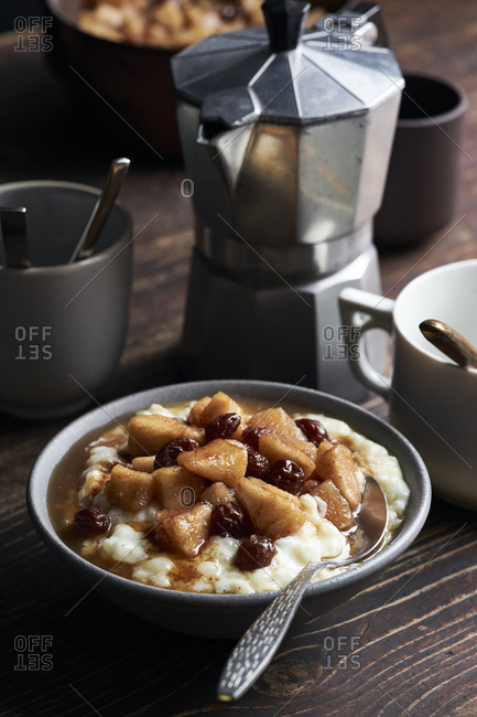 Bowl of rice pudding with apple-raisin compote on dark wooden table