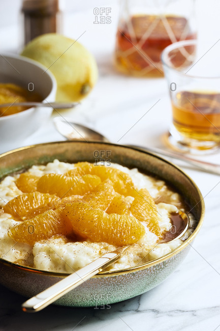 Sweet rice pudding with marinated oranges sprinkled with cinnamon in enameled bowl on white marble table