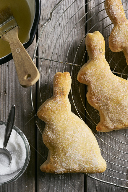 Traditional bunny-shaped cutout easter pastries sprinkled with sugar on rustic wooden table