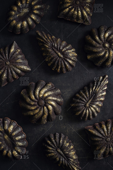 Mini chocolate cakes decorated with golden glitter on black vintage metal surface