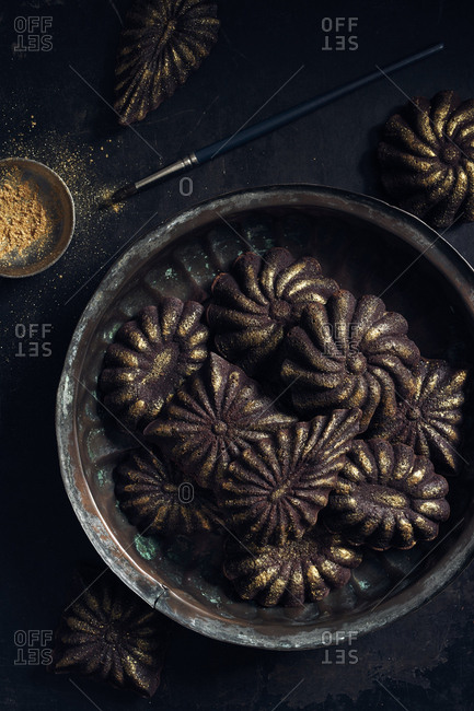 Mini chocolate cakes decorated with golden glitter on vintage copper plate