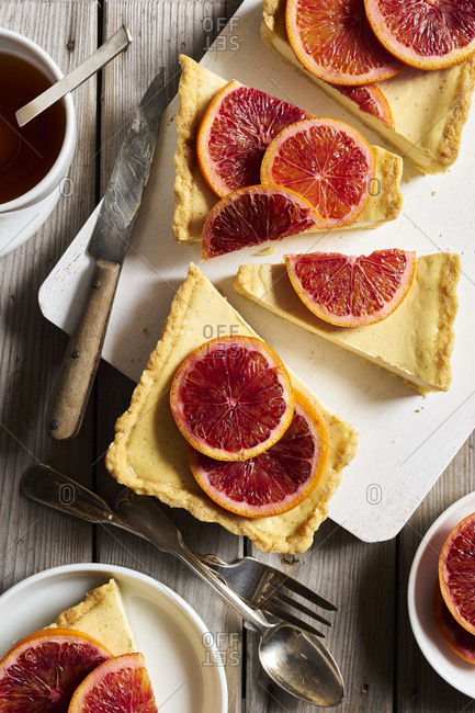 Yogurt vanilla tart with poached blood oranges served on cutting board on wooden table