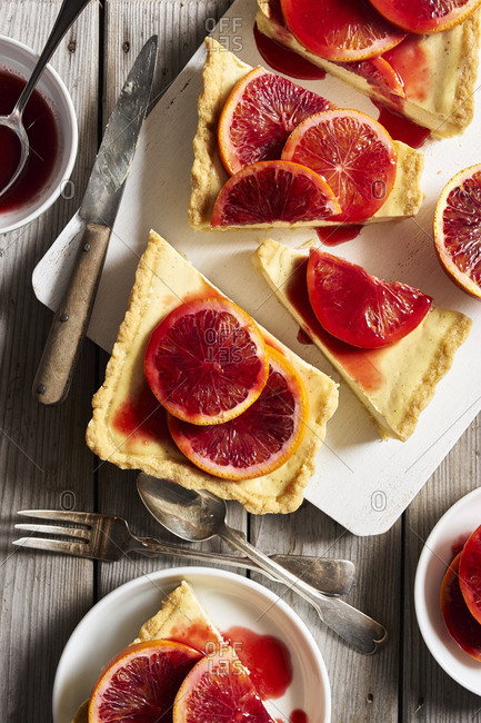 Yogurt vanilla tart with blood oranges served on cutting board