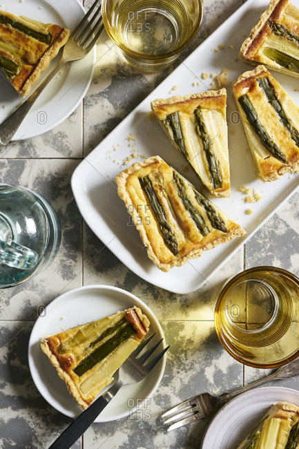 Rectangular green and white asparagus tart cut into slices