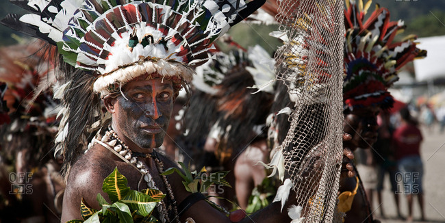 Alotau, Papua New Guinea - November 6, 2010:  A man with tribal face painting and wearing special clothing with feathers and leaves during the Kenu and Kundu Canoe Festival