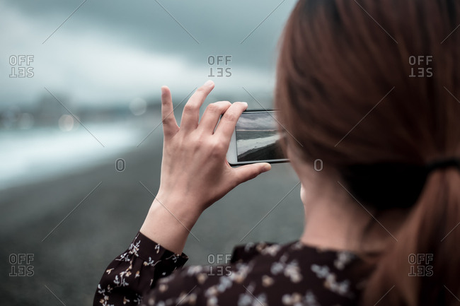 A woman taking a wave picture with a cell phone