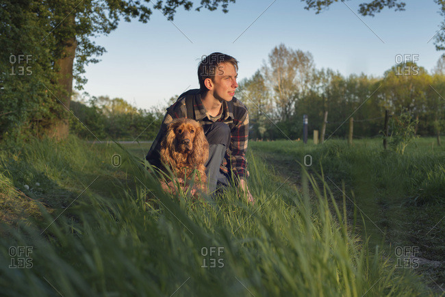 Teenage man with dog in countryside in evening sunlight