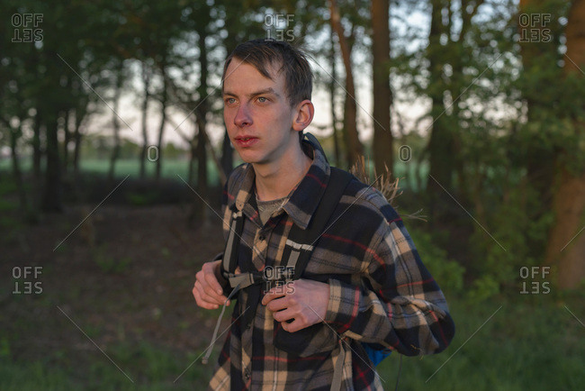 Teenage male hiker in backpack and checkered shirt in forest Lit by evening sunlight
