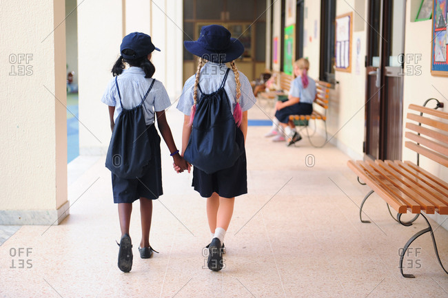 Two girls wearing school uniforms holding hands and walking side by side