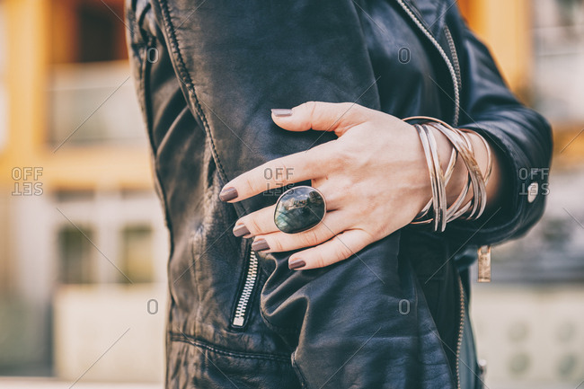 Detail shot of woman's hands, wearing a biker leather jacket and jewelry on her fingers