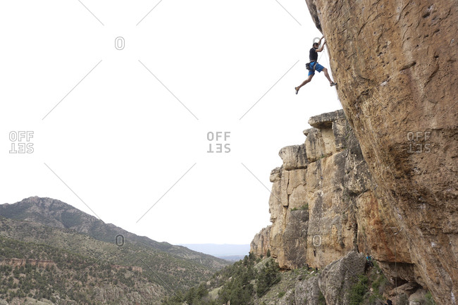 Low angle view of male hiker climbing mountain against clear sky
