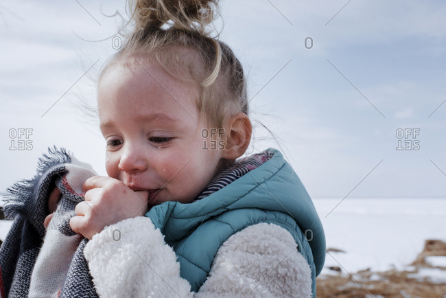 Close-up of crying girl sucking thumbs while standing against sky during winter