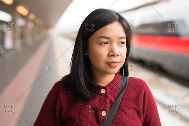 Portrait of an Asian young woman standing on the platform at a train station