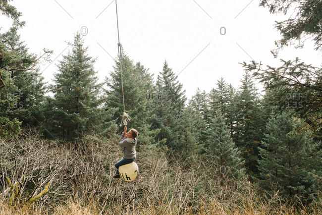Boy swinging on a buoy tied to a tree in the forest
