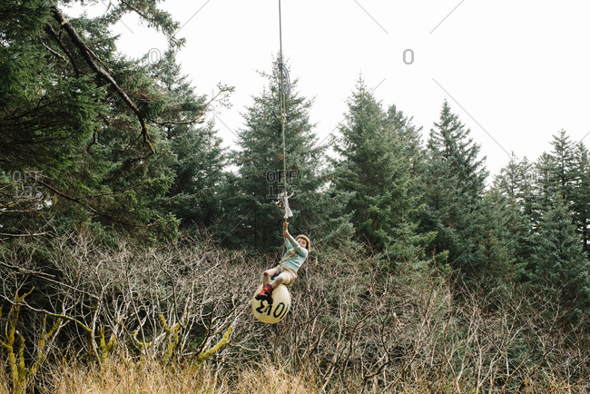 Little girl swinging on a buoy tied to a tree in the forest