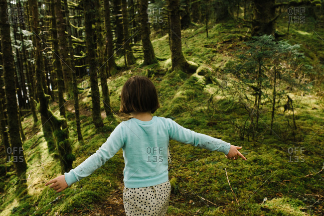Girl with outstretched arms hiking on a mossy trail through the forest on Kodiak Island