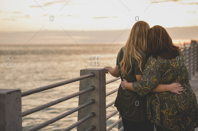 A lesbian couple stand arm in arm as they watch the sunset over the pier