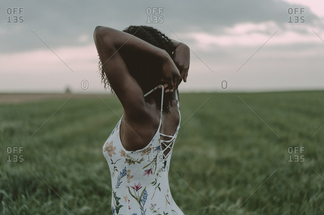 Young woman pulling on straps of her dress while standing in a field