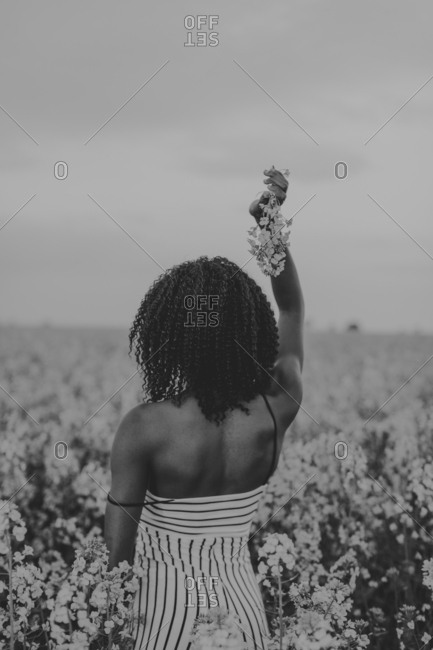Woman standing in a flower field and holding a bunch of wildflowers