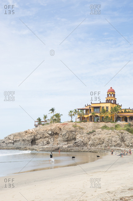 People relaxing on sandy beach below large house in Baja California, Mexico