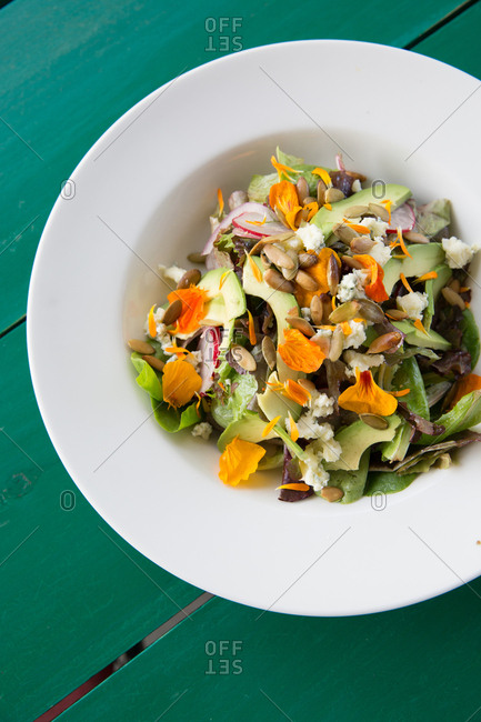 Salad topped with avocado slices and edible flowers
