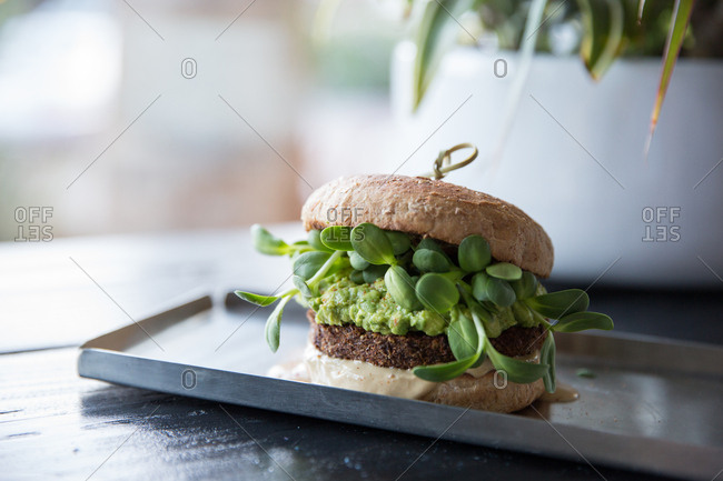 Veggie burger topped with guacamole and sunflower sprouts