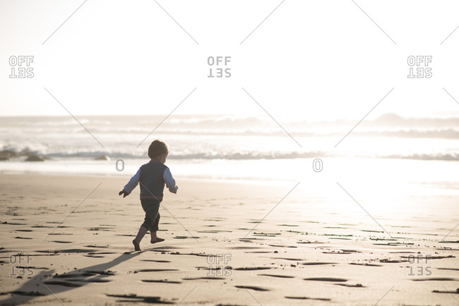 Little boy running on the beach - view from behind